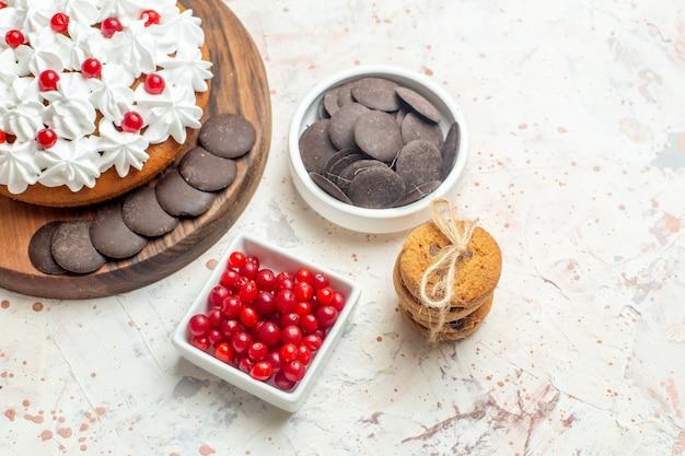 Onderste helft cake met witte room op snijplankkommen met bessen en chocoladekoekjes vastgebonden met touw op lichtgrijze tafel