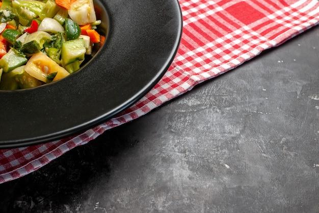 Onderste helft groene tomatensalade op ovale plaat een vork op donkere achtergrond