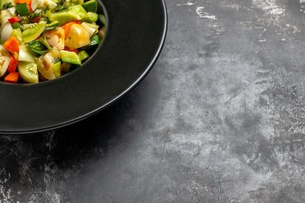 Onderste helft groene tomatensalade op ovale plaat op donkere vrije ruimte