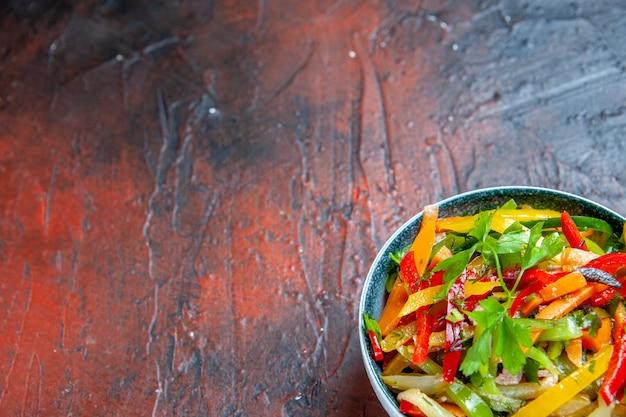 Onderste helft groentesalade in kom op donkerrode tafel met vrije plaats