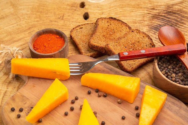 Onderste helft kaas op vork plakjes kaas op snijplank rode peper sneetjes brood zwarte pper in kom op houten tafel