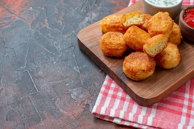 Onderste helft kipnuggets op houten bord met sauzen rood wit geruite keukenhanddoek op donkere tafel vrije ruimte