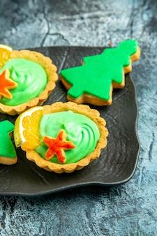 Onderste helft kleine taartjes met groene banketbakkersroom kerstboomkoekjes op zwarte plaat op grijs oppervlak
