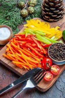 Onderste helft kleurrijke gesneden paprika's zwarte peper tomaten op snijplank zoutvork en mes pijnboomtakken op donkerrode tafel