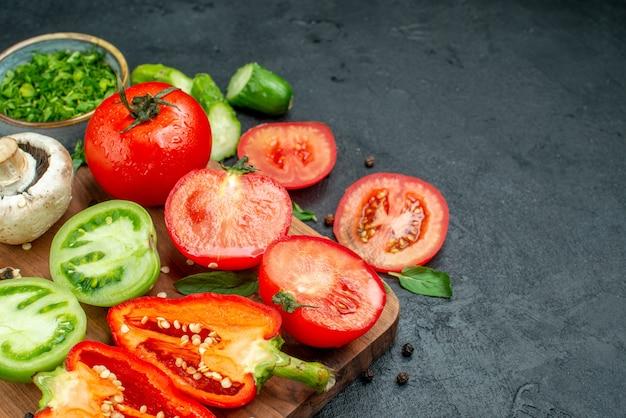 Onderste helft weergave groenten groene en rode tomaten paprika mes op snijplank greens in kom op zwarte tafel vrije ruimte