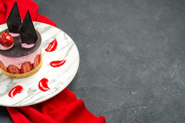 Onderste helft weergave heerlijke cheesecake met aardbei en chocolade op bord rode sjaal op donkere geïsoleerde achtergrond vrije plaats