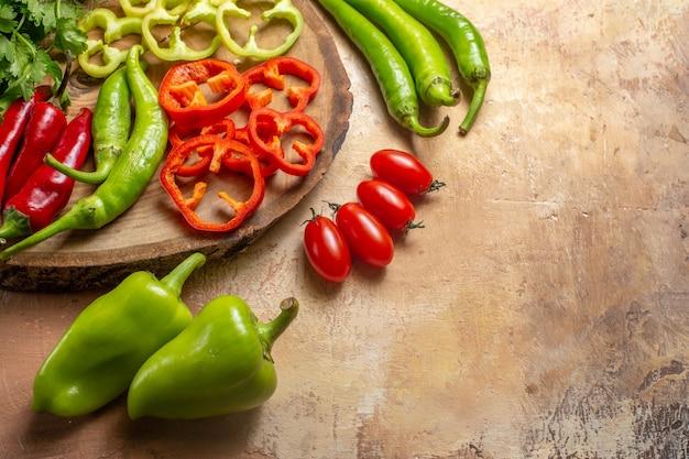 Onderste helft weergave verschillende groenten koriander hete pepers paprika in stukjes gesneden op ronde boom houten bord cherry tomaten paprika op gele oker achtergrond vrije ruimte