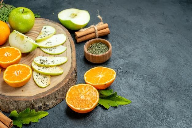 Onderste helft weergave verse appel en sinaasappelschijfjes op houten bord gedroogd muntpoeder in kom kaneelstokjes pijnboomtakken op zwarte tafel vrije ruimte
