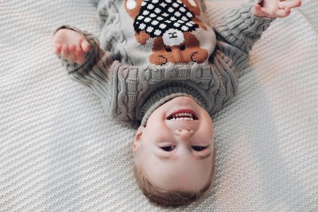 Ondersteboven foto van een schattige peuter op warme trui liggend op bed en lachen