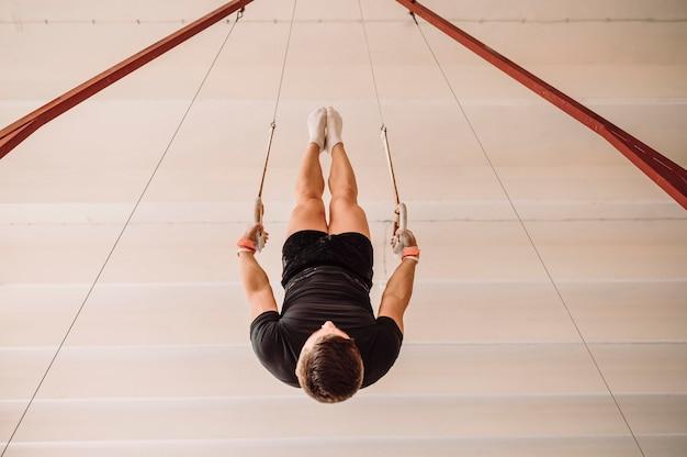 Ondersteboven jonge man uitoefenen op gymnastiek ringen