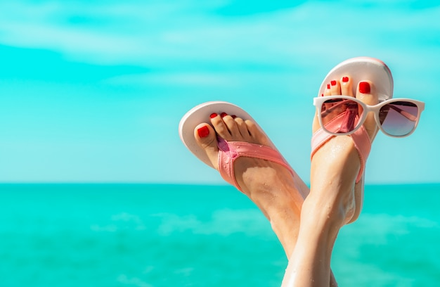 Ondersteboven vrouwenvoeten en rode pedicure die roze sandalen, zonnebril dragen bij kust. de grappige en gelukkige manier jonge vrouw ontspant op vakantie.