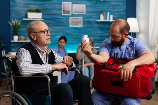 Ondersteun verpleegster die de behandeling van pillen uitlegt aan senior man