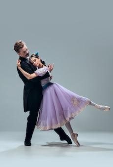 Ondersteunend. mooie eigentijdse ballroomdansers die op grijze studioachtergrond worden geïsoleerd. sensuele professionele artiesten die wals, tango, slowfox en quickstep dansen. flexibel en gewichtloos.