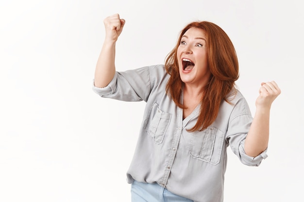 Ondersteunend opgewonden extreem gelukkig gelukkig roodharige vierende vrouw van middelbare leeftijd juichen zoon scoorde doel schreeuwen ja triomferen gebalde opgeheven vuisten vreugdevol overwinningsgebaar schreeuw witte muur