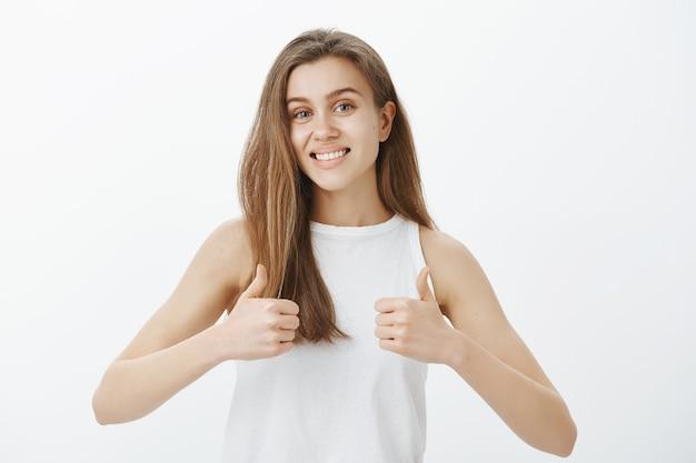 Ondersteunende aantrekkelijke vrouw die duimen omhoog laat zien, goede keuze prijzen, compliment maakt, ja zegt, goedkeurt