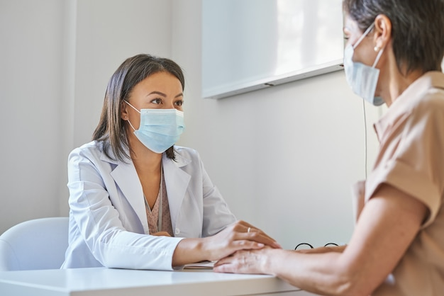 Ondersteunende afro-amerikaanse vrouwelijke arts in gezichtsbeschermend masker die de hand van de patiënt vasthoudt, zorg uitdrukt en troostende vrouw van middelbare leeftijd die kliniek bezoekt tijdens covid-19 pandemie en griepuitbraak