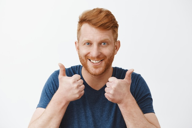 Ondersteunende en aantrekkelijke volwassen roodharige man met borstelharen die van een geweldig plan houden, handen opheffen, duimen opdagen en vreugdevol glimlachen