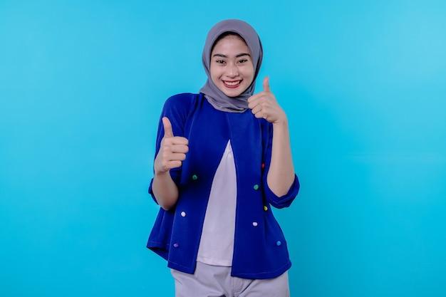 Ondersteunende en optimistische blije aardige aziatische vrouw die hijab draagt, duimen omhoog, onder de indruk en opgetogen