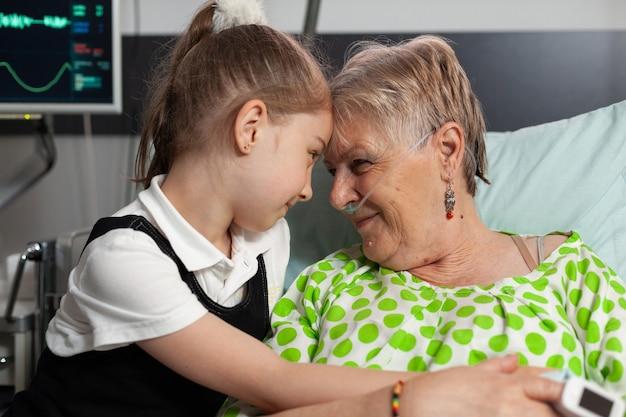 Ondersteunende kleindochter die voorhoofd aanraakt met bejaarde grootmoeder die liefde toont tijdens klinische rec...
