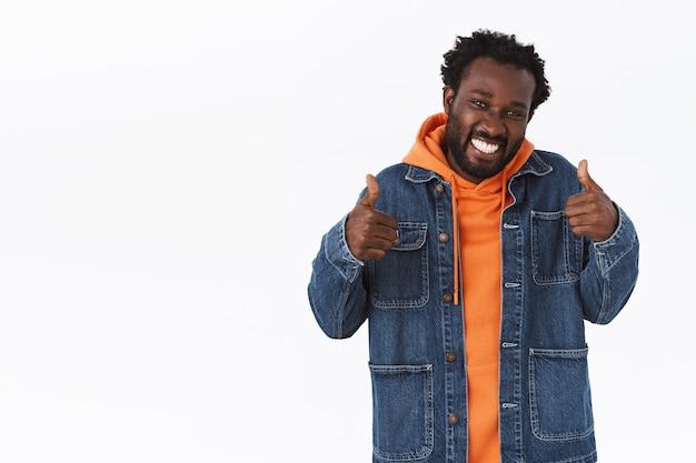 Ondersteunende knappe afro-amerikaanse man die duimen toont in like of goedkeuring, tevreden glimlacht, voor je wroet of zijn positieve antwoord geeft