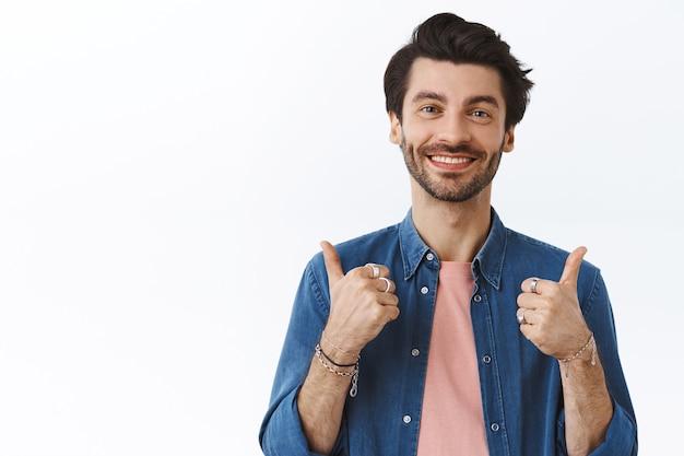 Ondersteunende, knappe charmante vriend met baard, duim omhoog en glimlachen als positieve feedback geven, je aanmoedigen alles goed, zoals idee, iets goeds goedkeuren, witte muur