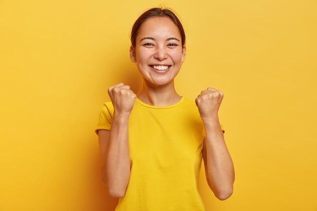 Ondersteunende knappe triomfeert met succes, steekt gebalde vuisten op, glimlacht gelukkig, heeft een oosterse uitstraling, is gelukkig eindelijk doel te bereiken, blij om dromen te vervullen, poseert nonchalant over gele muur