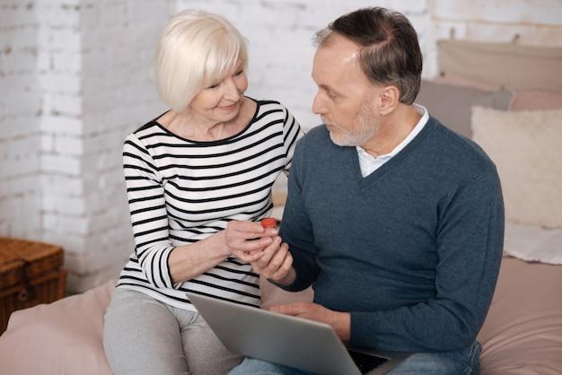 Ondersteuning geven. senior dame een remedie geven aan haar man met behulp van laptop zittend op bed.