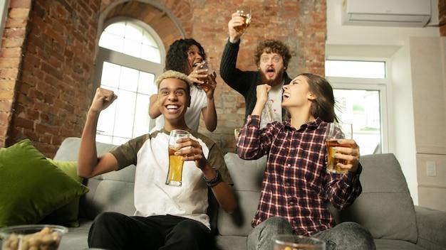 Ondersteuning. opgewonden mensen kijken naar sportwedstrijd, chsmpionship thuis. multi-etnische groep vrienden.