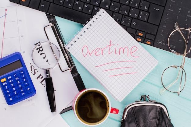 Onderstreept 'overwerk' op notebook met kantooraccessoires op houten tafelblad achtergrond. bovenaanzicht van dichtbij.