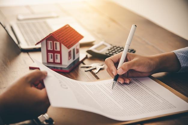 Ondertekenaars van het huis ondertekenen handtekening lening document voor eigenwoningbezit met eigendom van makelaars. hypotheek en vastgoedbeleggingen, woningverzekeringen