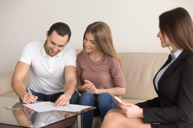 Ondertekening overeenkomst over ontmoeting met makelaar, paar kopen huurappartement