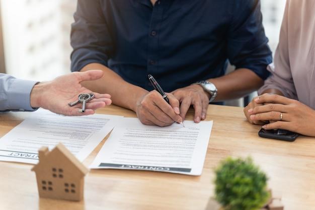 Ondertekening van een contract voor het kopen van huis in het kantoor van makelaar en makelaar in onroerend goed die sleutel van nieuw huis geven aan jong koppel in kantoor
