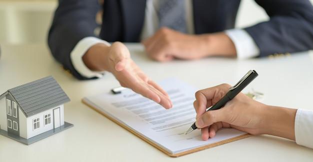 Ondertekening van een koopovereenkomst voor huis tussen de makelaar en de klant.