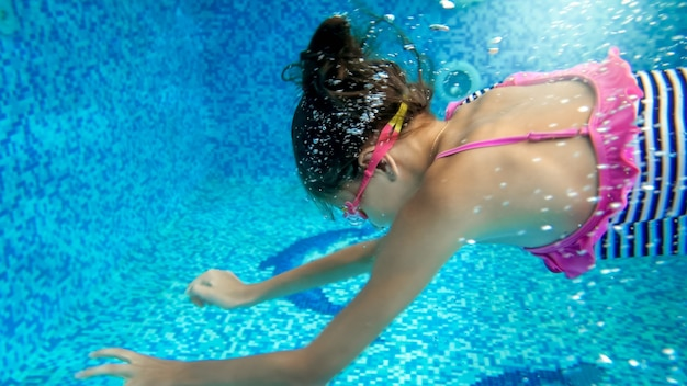 Onderwater close-up beeld van 10 jaar oud meisje dat zwemt en duikt in het zwembad
