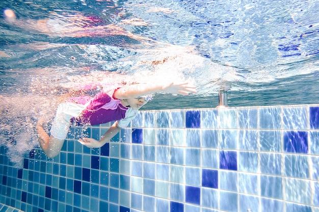 Onderwater jong klein schattig meisje zwemt in het zwembad met haar zwemleraar.