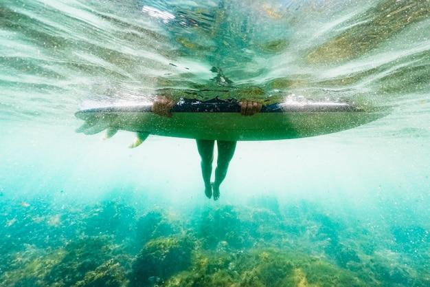 Onderwater schot van vrouw met surfplank