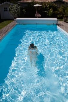 Onderwater vrouwenportret met witte bikini in zwembad.