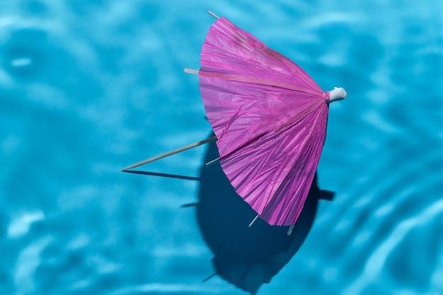 Onderwaterachtergrond met roze cocktailparaplu. blauw abstract oppervlak met zonlicht door water en kopieer ruimte. concept van reizen en vakantie