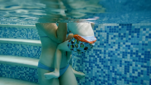 Onderwaterbeeld van jonge moeder die haar 3-jarige peuterjongen leert zwemmen in het zwembad