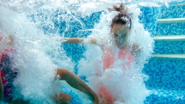 Onderwaterbeeld van twee tienermeisjes die in het zwembad van het zomerhotelresort springen