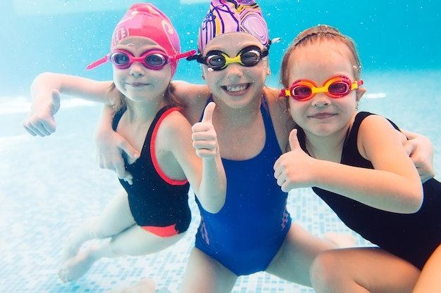 Onderwaterfoto van jonge vrienden in zwembad.