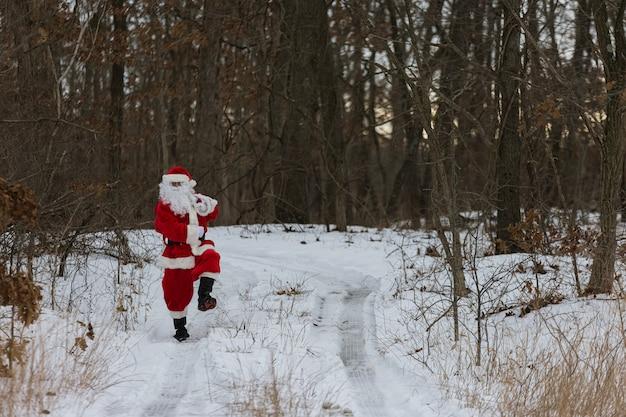 Onderweg draagt de kerstman kerstcadeautjes in het winterbos rond witte sneeuw