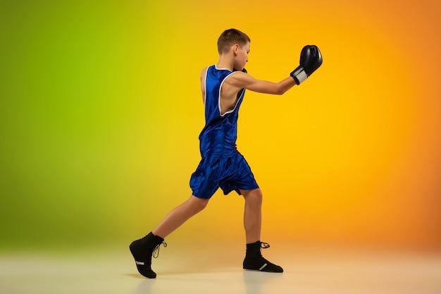 Onderweg. tiener professionele bokser training in actie, beweging geïsoleerd op verloop achtergrond in neonlicht. schoppen, boksen. concept van sport, beweging, energie en dynamische, gezonde levensstijl.
