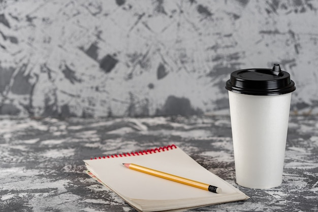 Onderweg werken. koffiekopje en blocnote op grijze stenen tafel. kopieer ruimte.