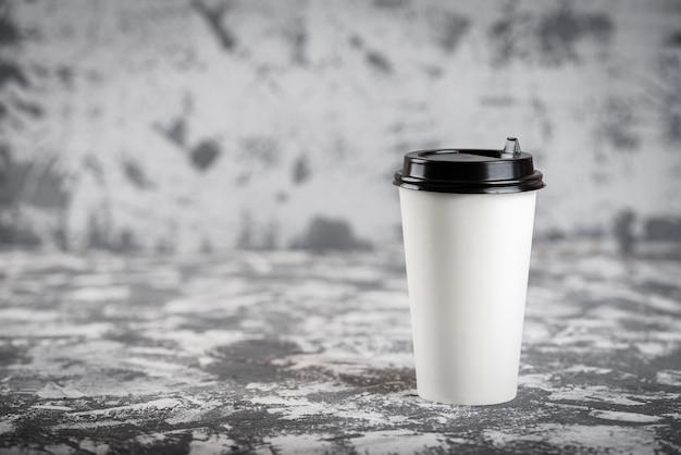 Onderweg werken. koffiekopje op grijze stenen tafel. kopieer ruimte.