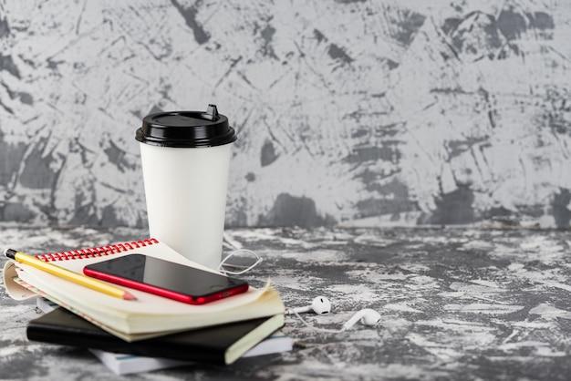 Onderweg werken of studeren. koffiekopje, mangofruit, rode smartphone en stapel blocnotes op grijze stenen tafel. kopieer ruimte.
