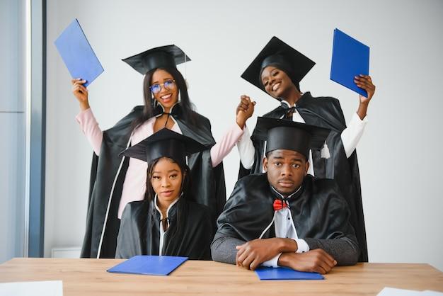 Onderwijs, afstuderen en mensen concept - groep gelukkige internationale afgestudeerde studenten in mortelborden en vrijgezellenjurken met diploma's