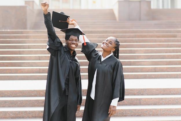 Onderwijs, afstuderen en mensen concept - groep gelukkige internationale studenten in mortel boards en bachelor toga met diploma's