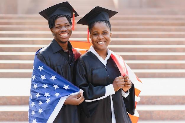 Onderwijs, afstuderen en mensenconcept - gelukkige internationale studenten in mortelborden en bachelorjurken met amerikaanse vlag