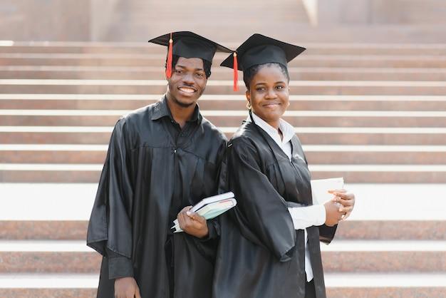 Onderwijs, afstuderen en mensenconcept - groep gelukkige internationale studenten in mortelborden en vrijgezellenjurken met diploma's